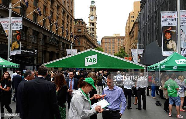 People queue up to bet on their favourite horses prior to the Melbourne Cup race at Martin Place in Sydney on November 5 2013 Race favourite Fiorente...