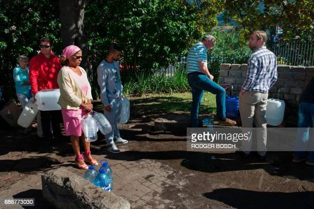 People queue up to collect drinking water from taps that are fed by a spring in Newlands on May 15 in Cape Town South Africa's Western Cape region...