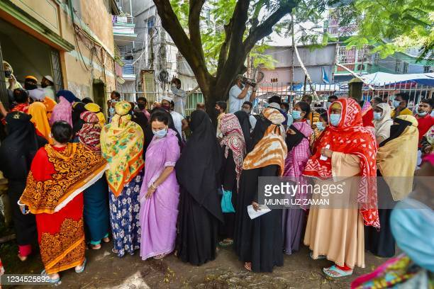 People queue up to get themselves inoculated with the Sinopharm Covid-19 coronavirus vaccine during a mass vaccination camp at Kholamora in...