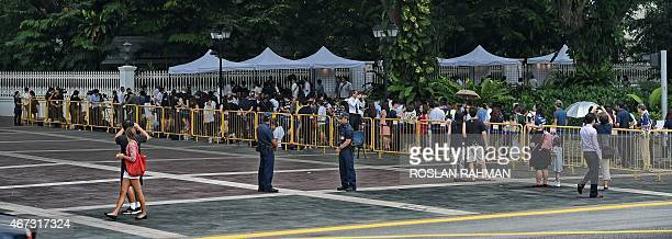 People queue up to pay tribute with messages and flowers at the entrance to the Istana presidential palace following the death of former prime...