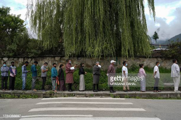People queue up to register themselves and get inoculated with the Covid-19 coronavirus vaccine at a temporary vaccination centre in Thimpu on July...
