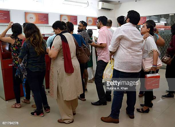 People queue up to use ATM machines after India's Prime Minister Narendra Modi announced the discontinuation of 500 and 1000 Rupee currency notes as...