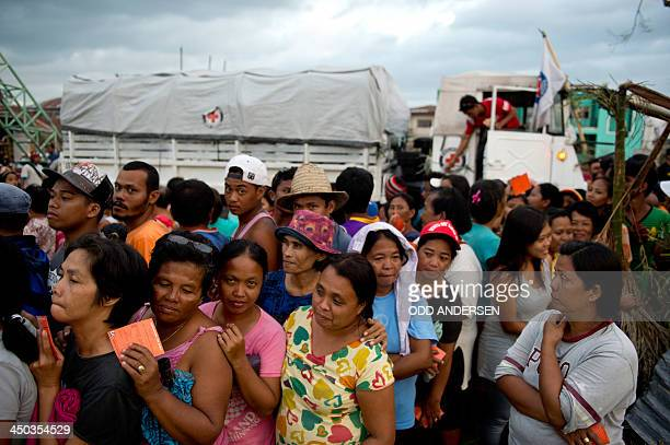 People queue up waiting for Red cross volunteers to distribute food parcels in Dagami some 35kms inland south of Tacloban on November 18 2013 The...