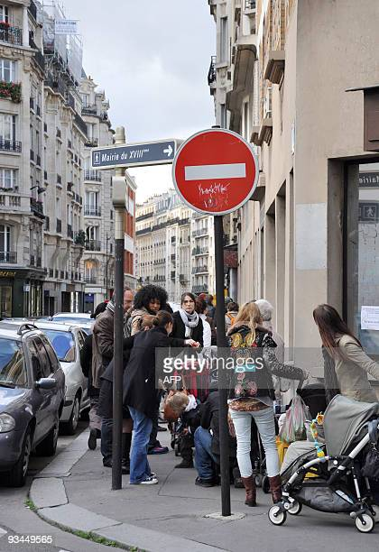 People queue with their children to be vaccinated against swine flu on November 27 2009 in Paris France's Health minister told today that children...