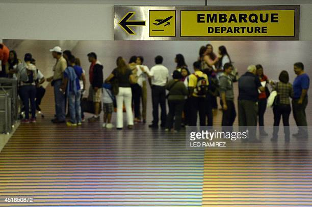 People queue with their luggage at the departure area of the Maiquetia international airport that serves Caracas on July 3 2014 A survey by pollster...
