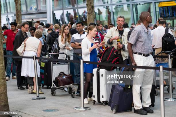 People queue with their luggage outside Heathrow Airport Terminal 5 on May 28 2017 in London England Thousands of passengers face a second day of...