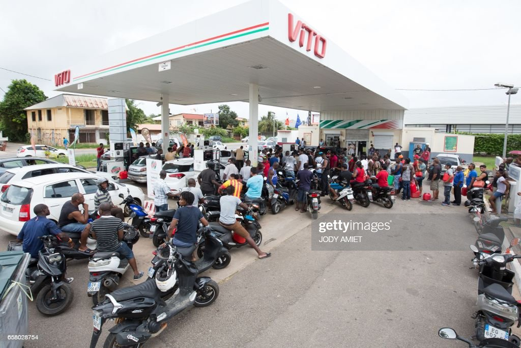 People queue with vehicles and jerrycans after a tank truck was able to resupply an out-of-fuel petrol station on March 26, 2017, in Cayenne, French Guiana, during a string of region-wide protests and road blockades. Road blockades in French Guiana were letting traffic through on March 26 to allow people to replenish in food and petrol on the eve of a general strike. Workers in several sectors, including the energy giant EDF and public hospitals, have launched protests this week demanding pay raises and improved public safety and health coverage. PHOTO / jody amiet