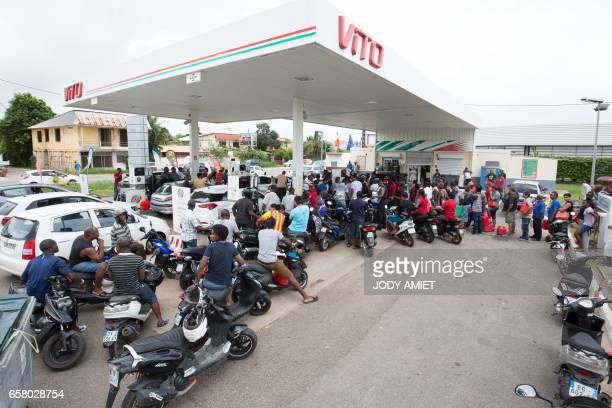 People queue with vehicles and jerrycans after a tank truck was able to resupply an outoffuel petrol station on March 26 in Cayenne French Guiana...