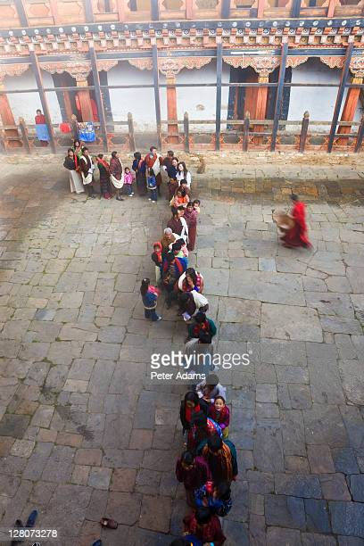 people queueing to be blessed, jakar dzong, monastery, jakar, bumthang, bhutan - peter adams stock pictures, royalty-free photos & images