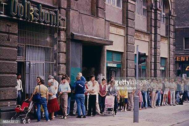 People queuing at the Volksbank to exchange their currency on the first day of the reunification of Germany East Berlin 1990 The Deutsche Mark is...
