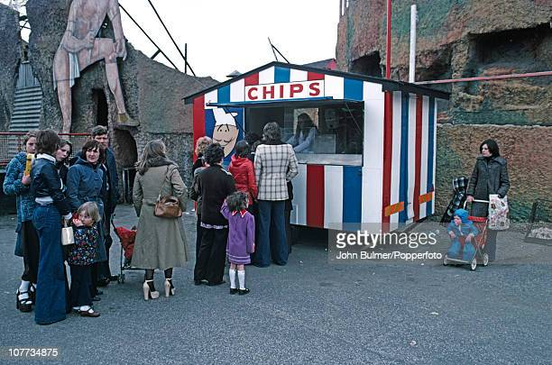 People queuing for chips at a snack stand in front of the scenic railway at Belle Vue amusement park in Manchester England in 1976