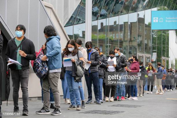 People queuing for the first dose of Pfizer Covid-19 vaccine being offered to adults over the age of 18 at Tottenham Hotspur Stadium as the capital...