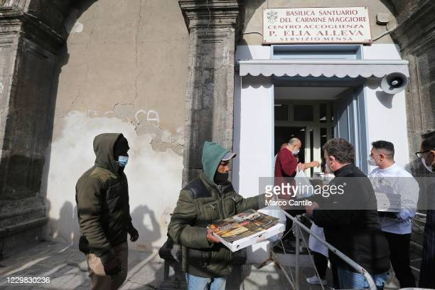People queuing in front of the Caritas in Carmine square in Naples, while they receive a meal and pizza, during the Pizza Solidale initiative, the...