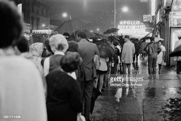 People queuing in the rain for an Isaac Hayes concert at the Apollo Theater on West 125th Street, New York City, 26th June 1970.