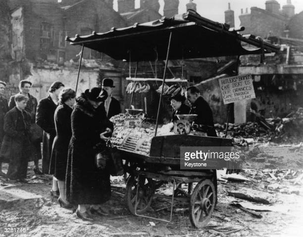 People queuing to buy oranges and bananas at a stall in bombwrecked London during the Blitz 23rd November 1940 A sign on the stall reads 'Hitler's...