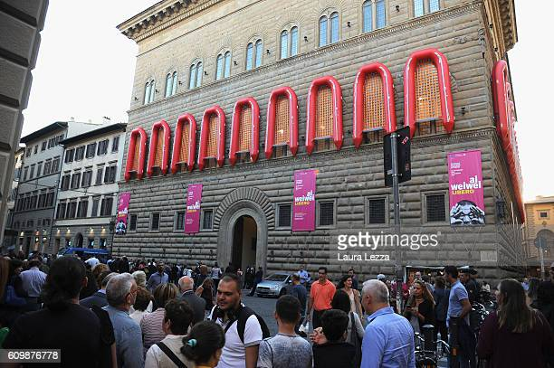 People queuing while an installation by the Chinese artist Ai Weiwei featuring 22 rubber boats dedicated to the refugees who risk their lives to...