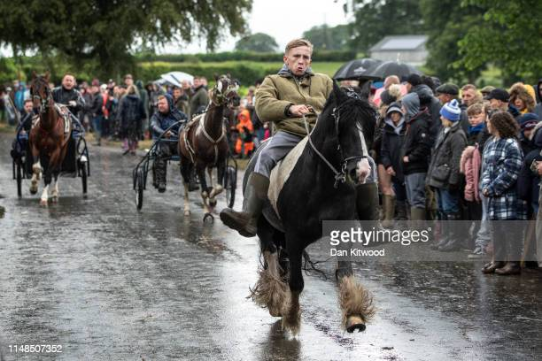 People race their horse and carts down the 'mad mile' in heavy rain during the annual Appleby Horse Fair on June 08, 2019 in Appleby-in-Westmorland,...