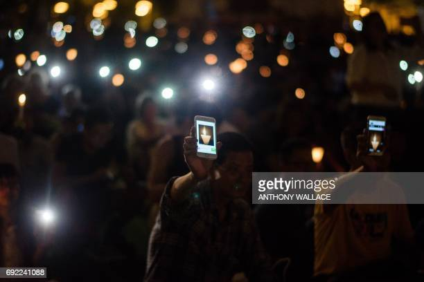 People raise candles and smartphones showing an animated GIF image of a candle in Hong Kong's Victoria Park on June 4 during a vigil to mark the 28th...