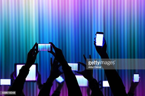 people raise his bright smartphone and tablet device during a night show celebration with dark silhouettes and colorful background. - actuación conceptos fotografías e imágenes de stock