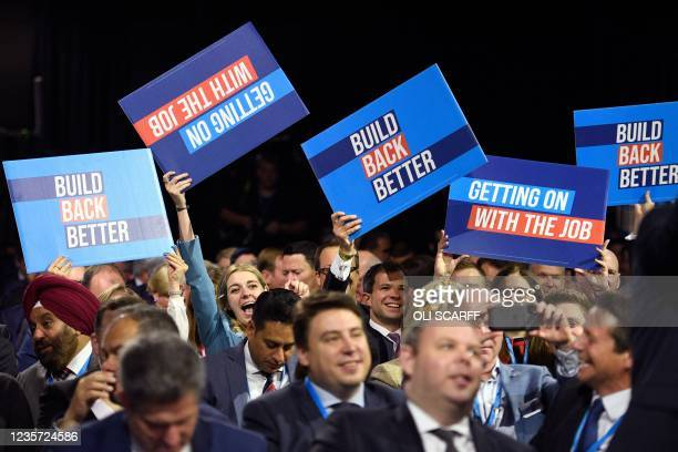 People raise placards as they wait for the keynote speech of Britain's prime minister at the Manchester Central convention centre on the final day of...