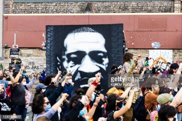 People raise their fist during a demonstration near the George Floyd Memorial in Minneapolis, Minnesota on April 18, 2021. - Kim Potter, a 26-year...