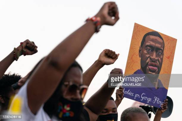 People raise their fists and hold a portrait of George Floyd during a rally following the guilty verdict the trial of Derek Chauvin on April 20 in...