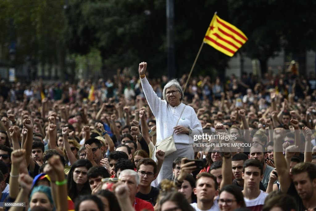 TOPSHOT - People raise their fists during a protest in Barcelona on October 2, 2017 a day after hundreds were injured in a police crackdown during Catalonia's banned independence referendum. /