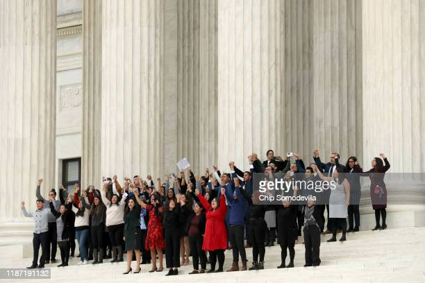People raise their fists in the air and cheer on the steps of the US Supreme Court after attending arguments in a case about the Deferred Action on...