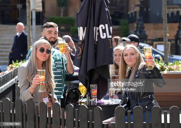 People raise their glasses as pubs with outdoor facilities reopen on April 30, 2021 in Belfast, Northern Ireland. Non essential retail shops and bars...