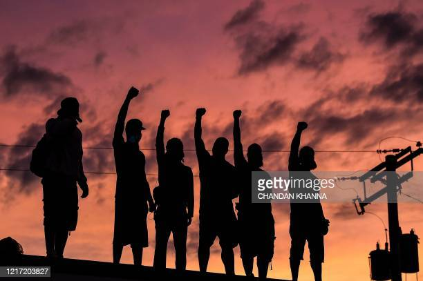 TOPSHOT People raise their hands and shout slogans as they protest at the makeshift memorial in honour of George Floyd on June 2 2020 in Minneapolis...