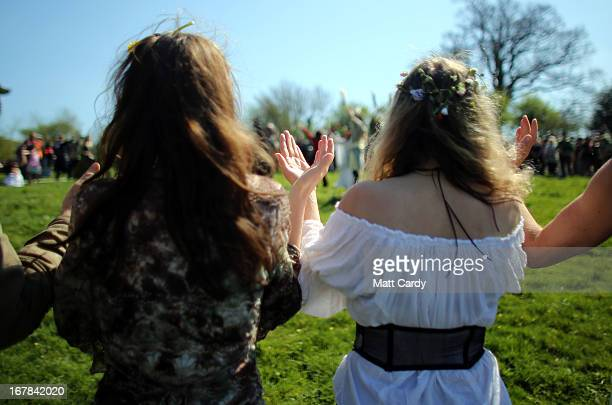 People raise their hands as form a circle and take part in a Beltane May Day celebration in Glastonbury main street on May 1 2013 in Glastonbury...