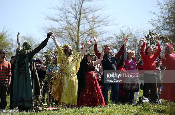 People raise their hands as they form a circle and take part in a Beltane May Day celebration below Glastonbury Tor on May 1 2013 in Glastonbury...