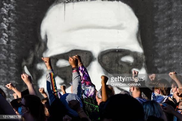 TOPSHOT People raise their hands as they protest at the makeshift memorial in honour of George Floyd on June 4 2020 in Minneapolis Minnesota On May...