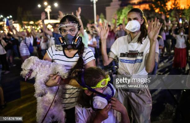 People raise their hands as they wear masks during a protest in front of the Romanian Government headquarters in Bucharest August 17 2018 Hudreds of...