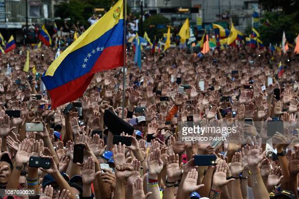 TOPSHOT People raise their hands during a mass opposition rally against President Nicolas Maduro in which Venezuela's National Assembly head Juan...
