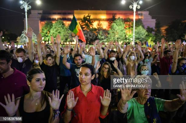 People raise their hands during a protest in front of the Romanian Government headquarters in Bucharest on August 17 2018 Hundreds of protesters...