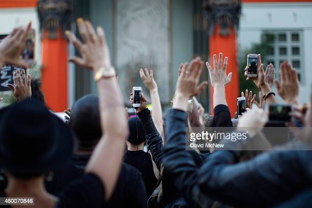 People raise their hands in front of the TCL Chinese Theatre as they march on Hollywood Boulevard to protest of the decision in New York not to...