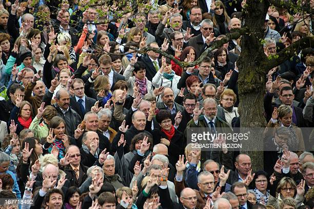 People raise their hands to vote during the annual Landsgemeinde meeting in a square in the town of Appenzell eastern Switzerland on April 28 2013...