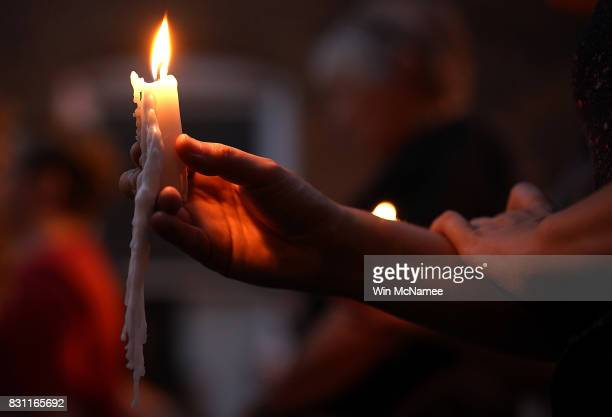 People raise their memorial candles during a vigil at the location where 32yearold Heather Heyer was killed when a car plowed into a crowd of people...