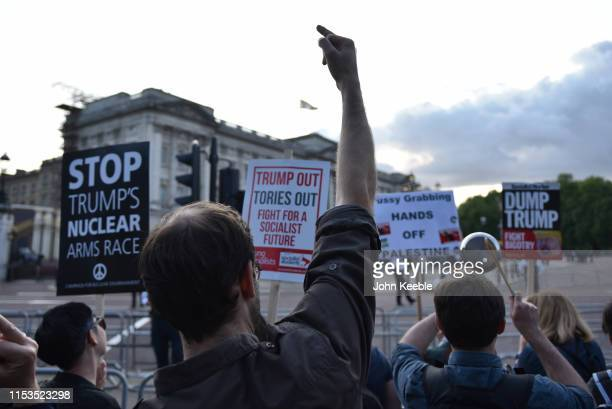 People raise their middle finger during a protest over Donald Trump's state visit outside Buckingham Palace on June 03 2019 in London England...