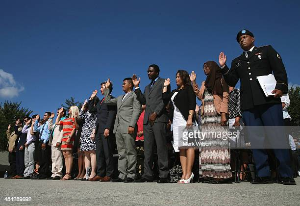 People raise their right hands as they are administered the Oath of Allegiance to become US citizens during a naturalization ceremony at the Dr...