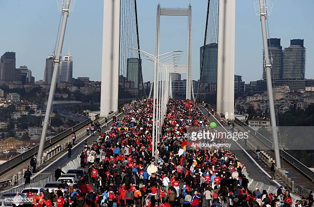 People raise Turkish flags as Athletes and thousands of people take part in the 38th Vodafone Istanbul Marathon the worlds only road race where...