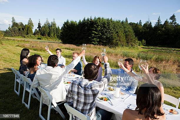 people raising glasses at dinner party on a farm - farm to table stock photos and pictures