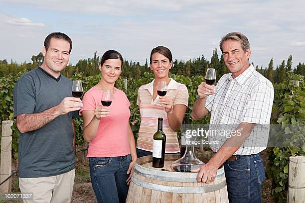People raising glasses of wine at vineyard