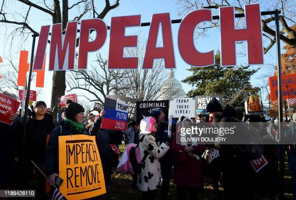 TOPSHOT People rally in support of the impeachment of US President Donald Trump in front of the US Capitol as the House readies for a historic vote...