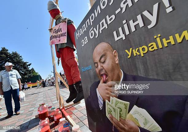 People rally near installation depicting a hanging dummy symbolic blood in bottles and placard showing a banker counting money signed 'Excess profits...