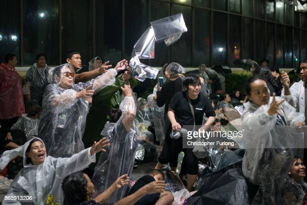 People reach out for free plastic sheeting to cover them from torrential rain as they begin to queue and sleep on the streets overnight to attend...