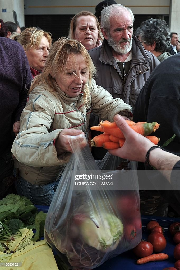 People reach out reach out for a bags of fruit and vegetables during a free distribution by Greek farmers outside the Agriculture Ministry in Athens part a farmers protest against high production c...