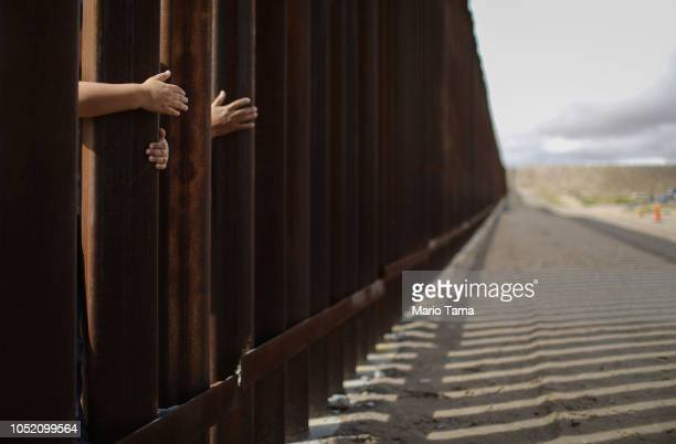People reach through the wall from the Mexican side at the conclusion of the Hugs Not Walls event on the USMexico border on October 13 2018 in...