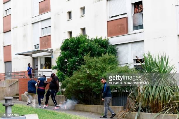 People react after French gendarmes throw tear gas on residents at the Breil neighbourhood in Nantes on July 4 2018 Groups of young people clashed...